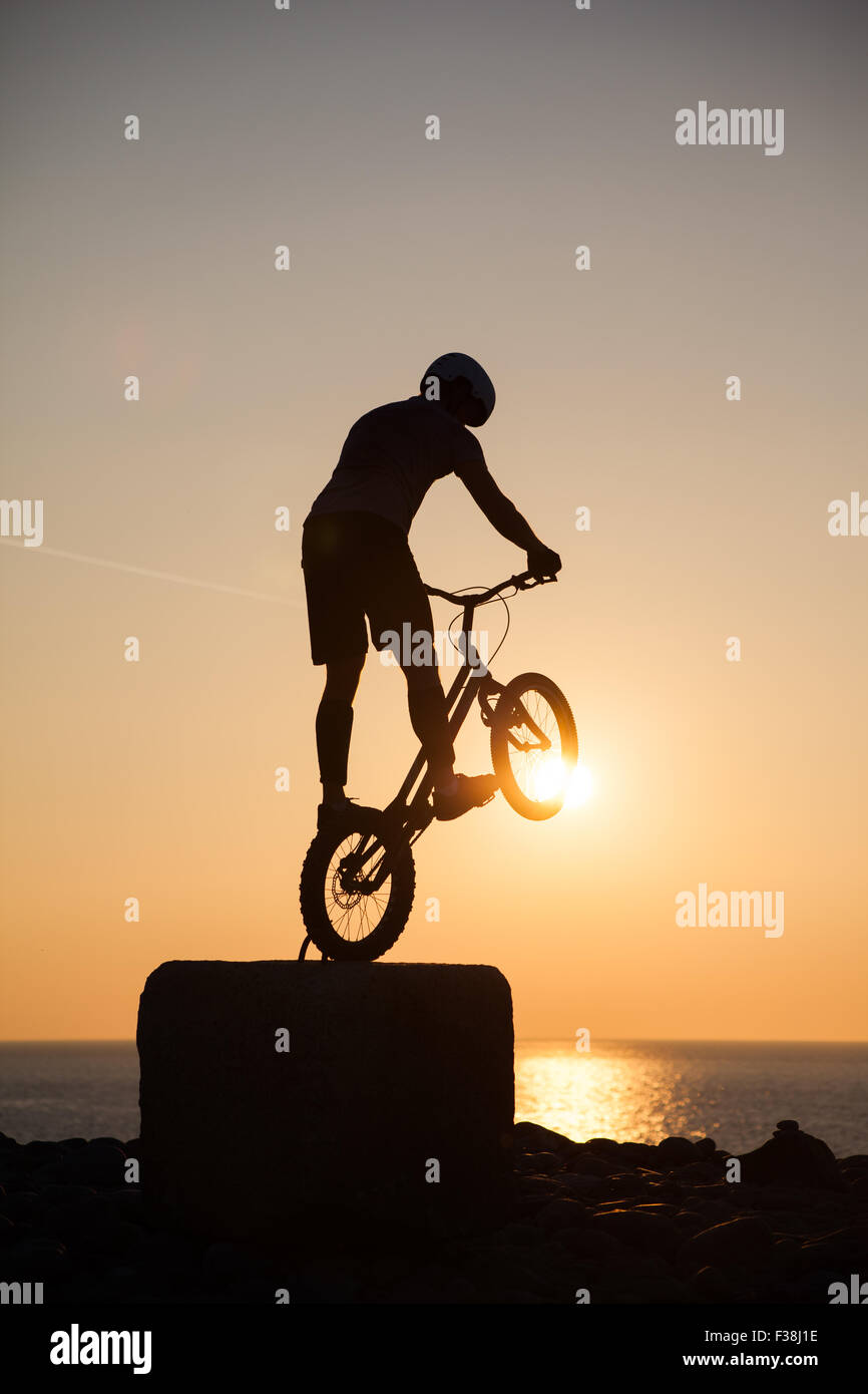 A silhouetted man performing freestyle riding at sunset in Aberystwyth Stock Photo