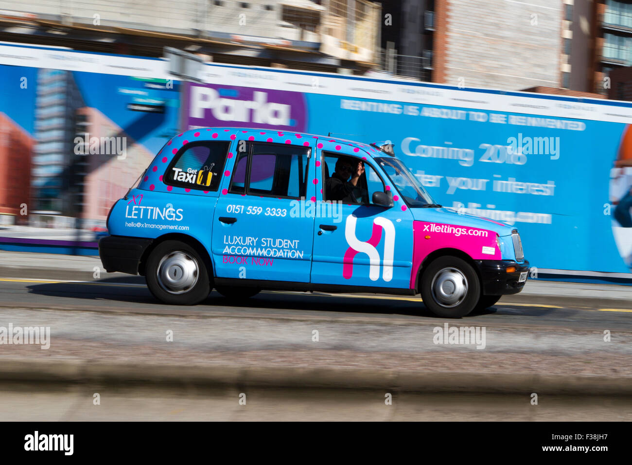 A blurred moving LT1 hackney cab taxi at speed motion blur on 'The Strand' at Liverpool One, Liverpool, - Stock Image