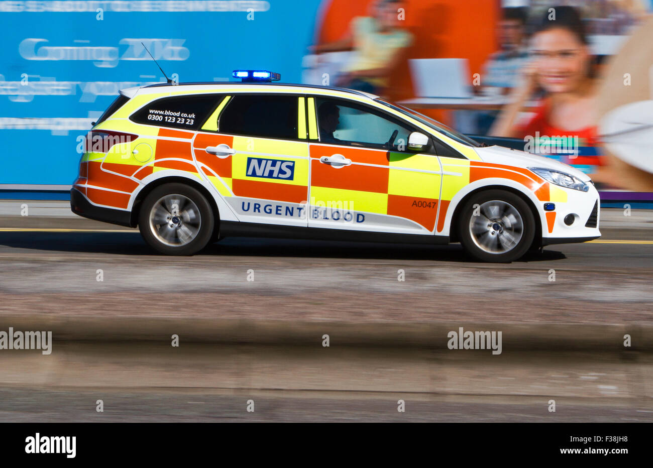 A blurred urgent blood response vehicle with sirens and blue lights speeding through Liverpool City Centre, Merseyside, - Stock Image