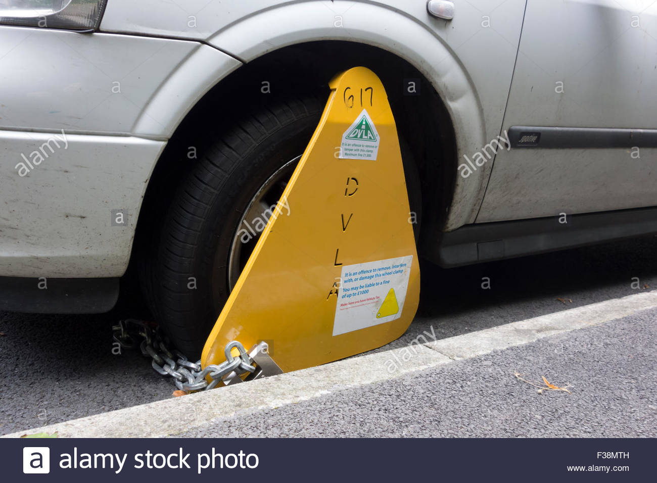 A DVLA wheel clamp on an untaxed vehicle on the streets of Sheffield, England, UK Stock Photo