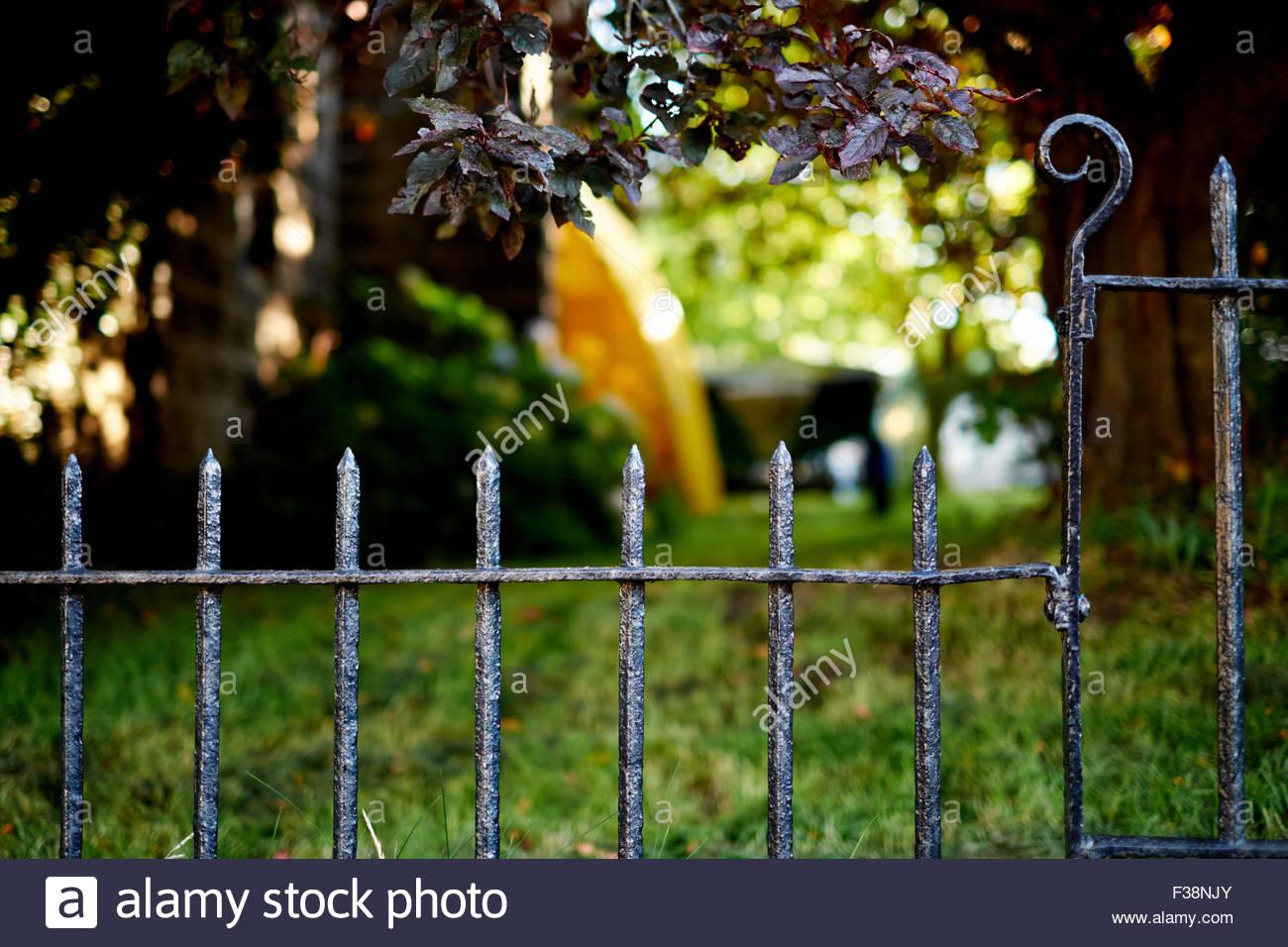 Sunlit garden behind cast iron railings - Stock Image