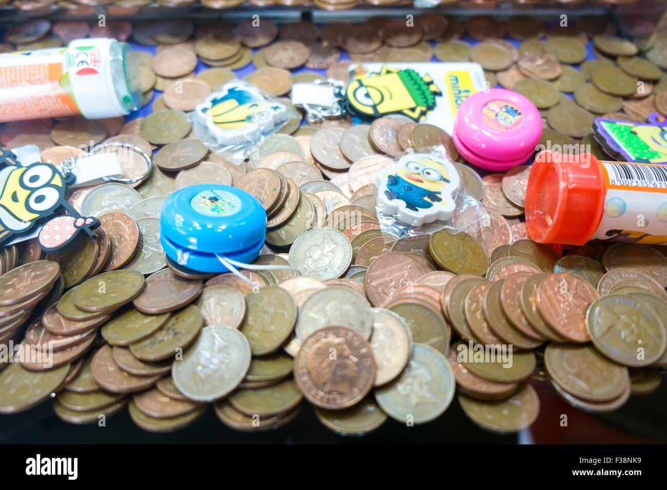 Coins in a penny drop arcade machine. - Stock Image
