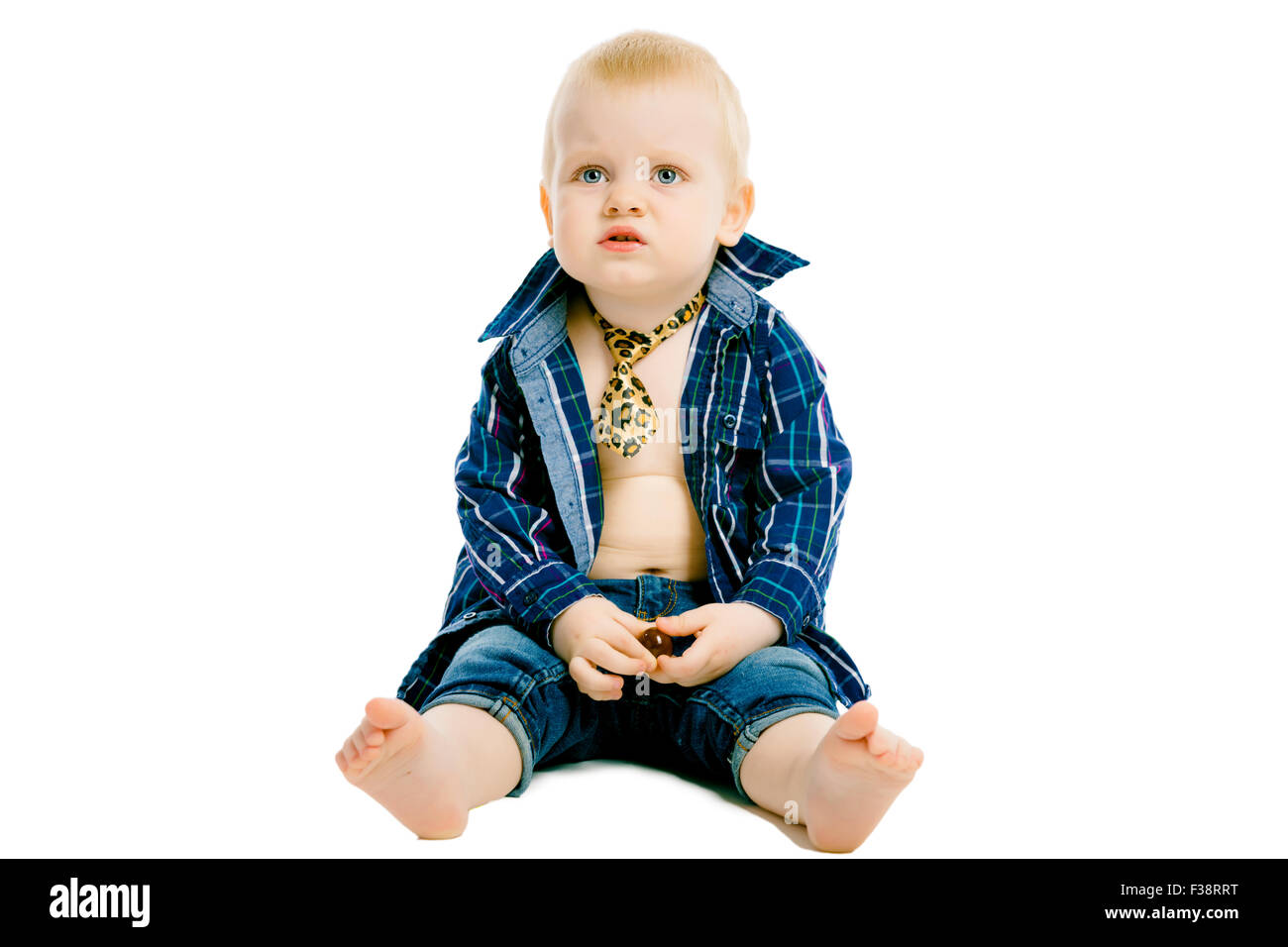 Little dissatisfied boy in a plaid shirt, tie and jeans on a white background - Stock Image
