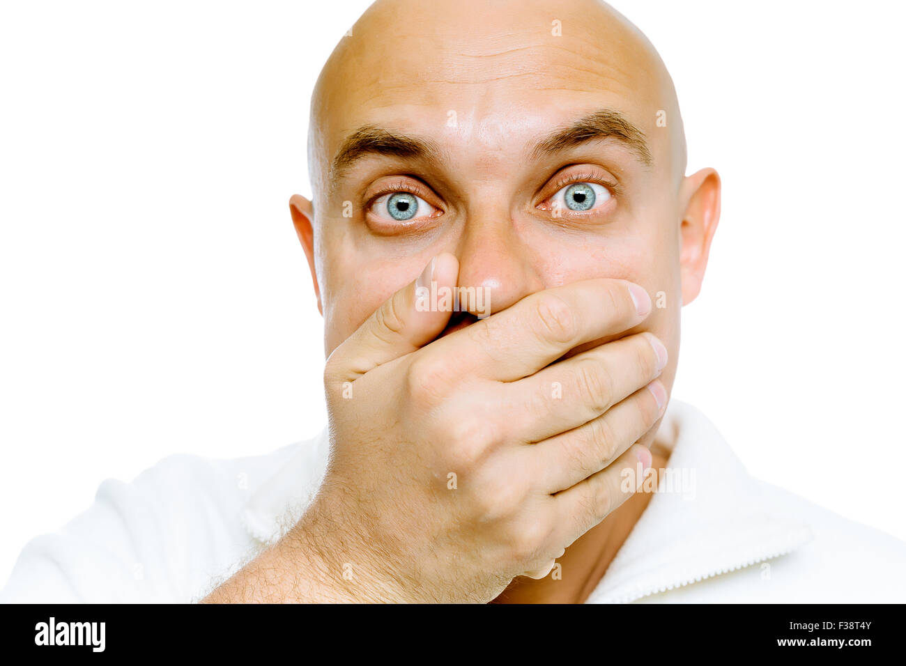 Bald blue eyes frightened man in a white jacket covers her mouth with his hand. Studio. isolated - Stock Image