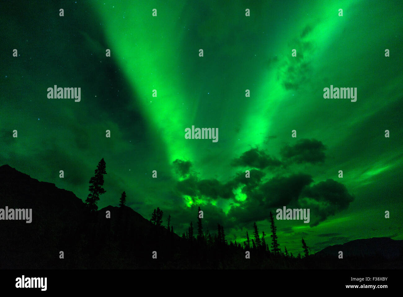 The Northern Lights emerge through the clouds in remote Alaska - Stock Image