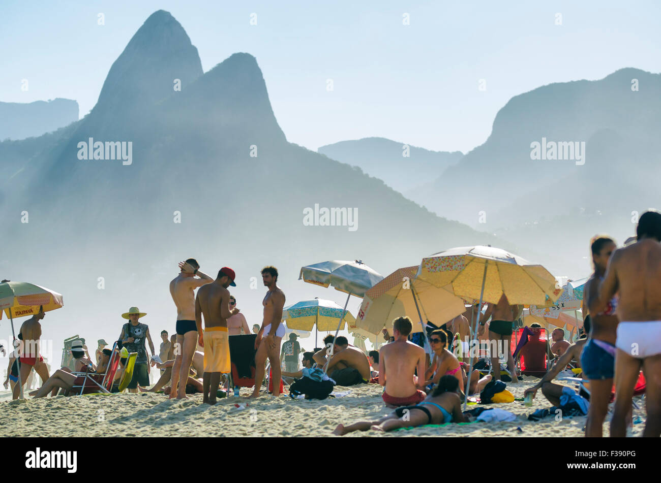 RIO DE JANEIRO, BRAZIL - JANUARY 20, 2013: Locals and visitors crowd Ipanema Beach against the iconic Two Brothers - Stock Image