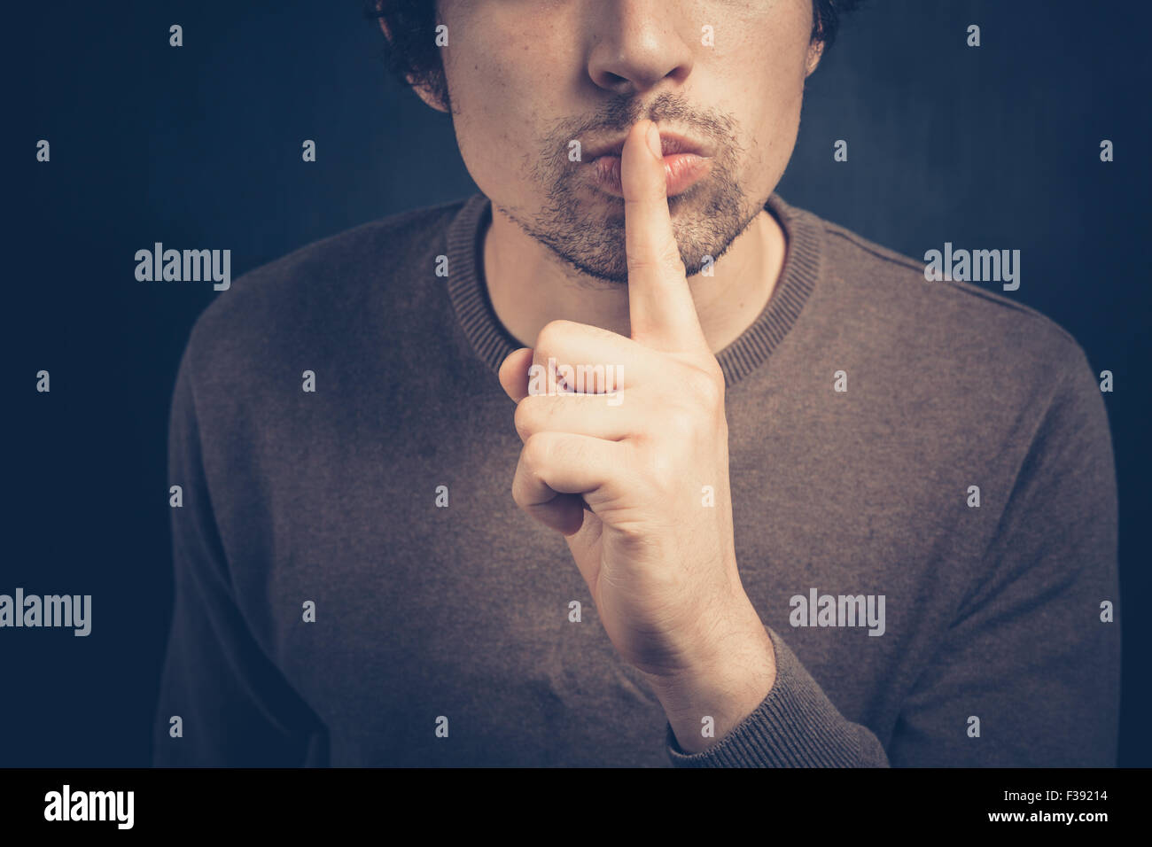 Young man is signalling hush with his finger on his lips - Stock Image