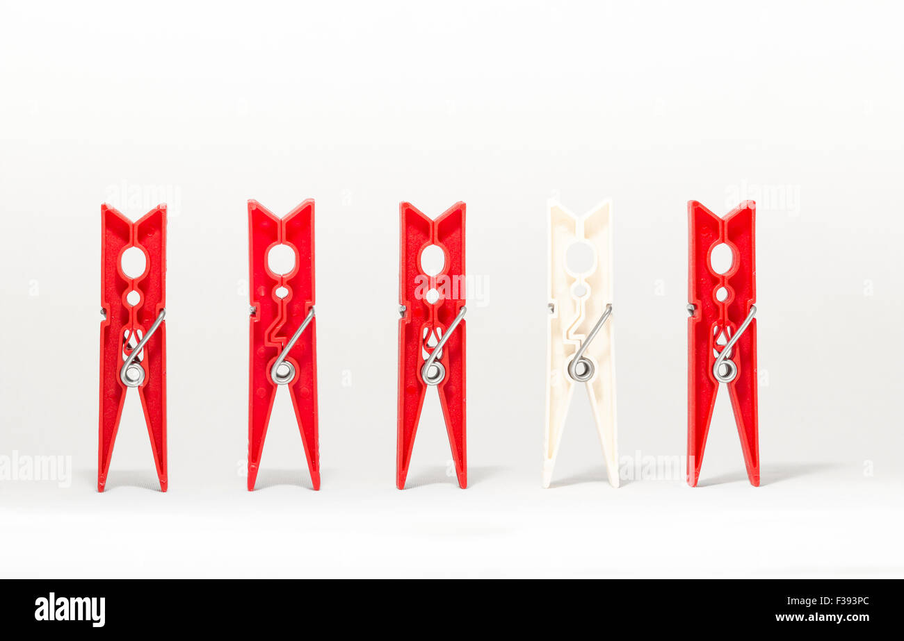clothespins on white background representing differences of race - Stock Image