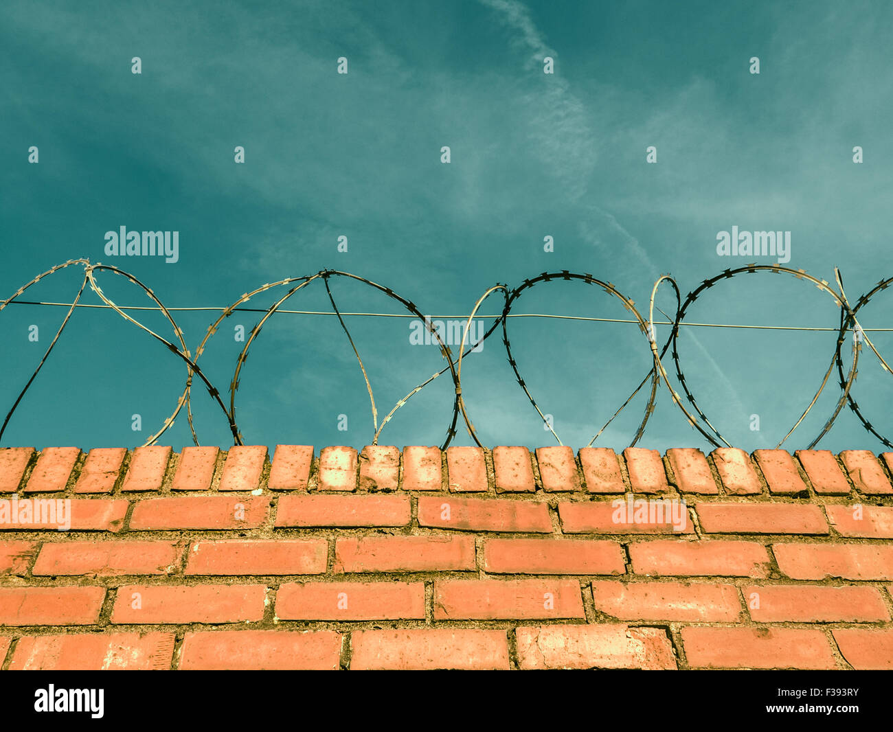 Barbed Or Razor Wire On Top Of A Red Brick Wall Around Private Property - Stock Image
