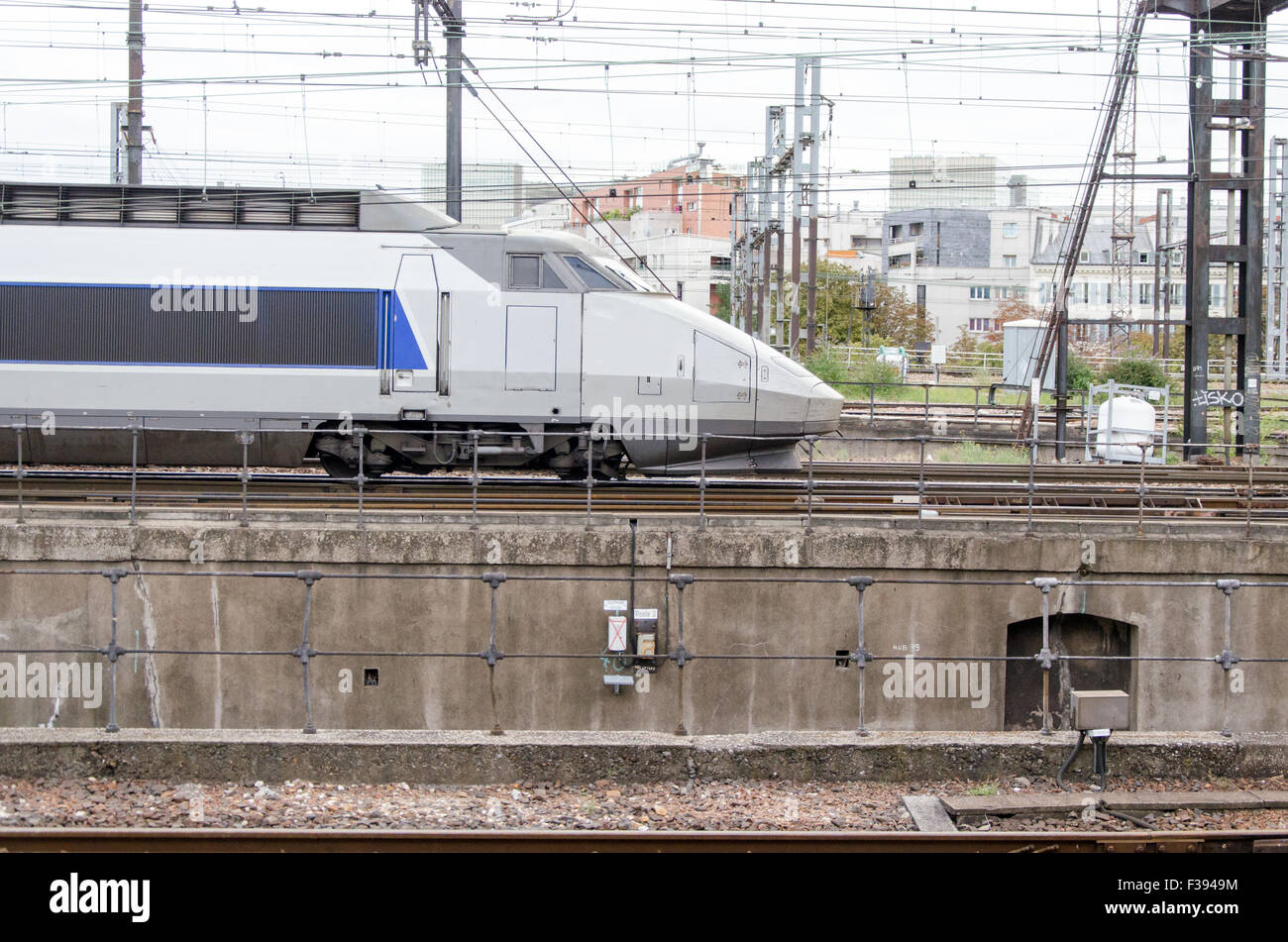 Blue and grey high-speed train on an urban background railway station - Stock Image