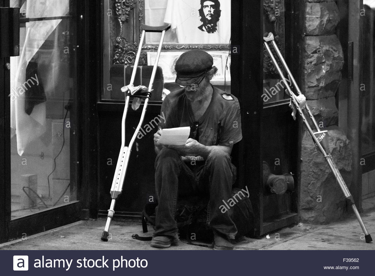 Black and white image of an old man in torn clothes writing on paper with underarm crutches by his side. Disabled Stock Photo