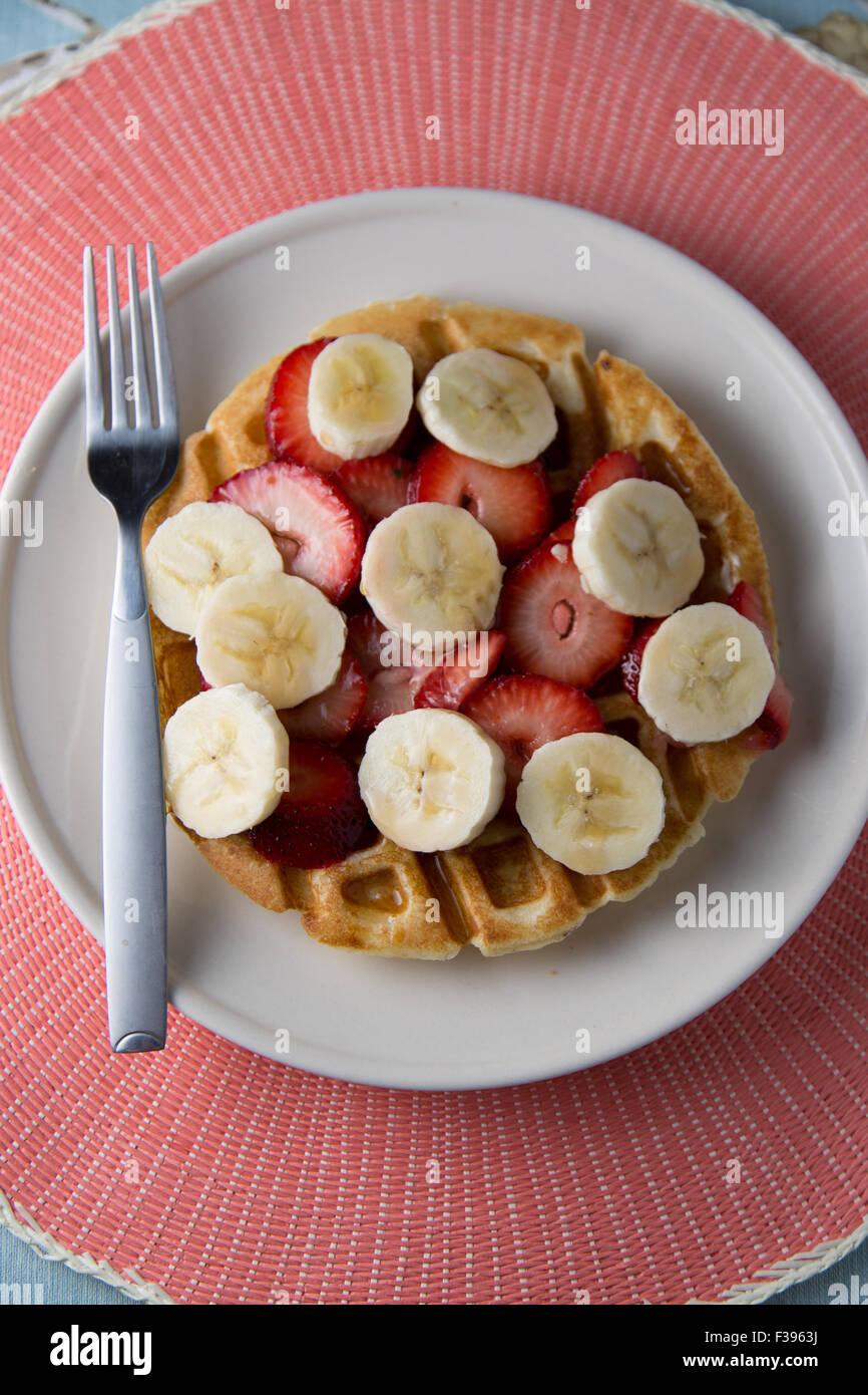 Waffle with strawberries and banana slices - Stock Image