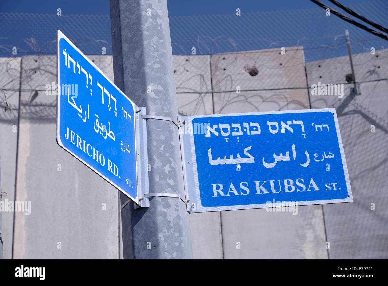 Street signs in Hebrew English and Arabic next to the massive separation wall built by Israel in Abu Dis a Palestinian - Stock Image