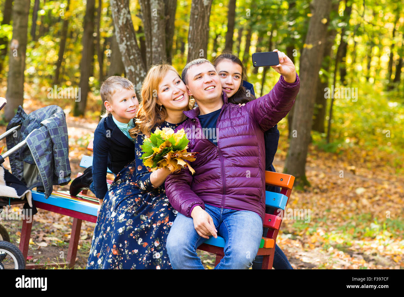 family, childhood, season, technology and people concept - happy family taking selfie with smartphone in autumn - Stock Image
