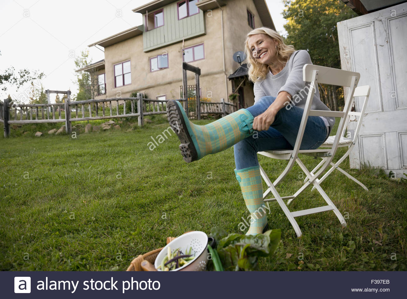 Smiling woman putting on wellies in garden - Stock Image