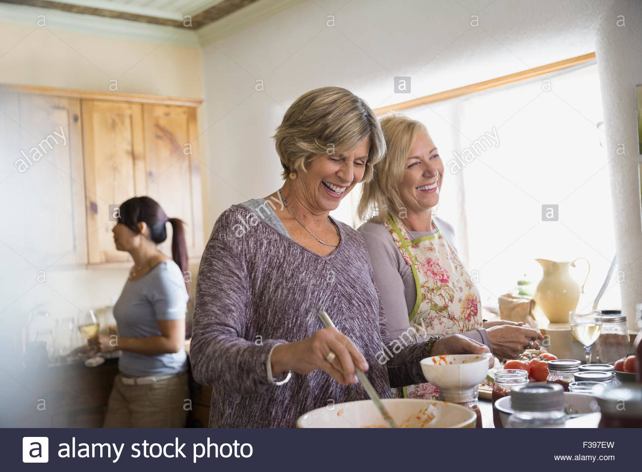 Laughing women canning in kitchen - Stock Image
