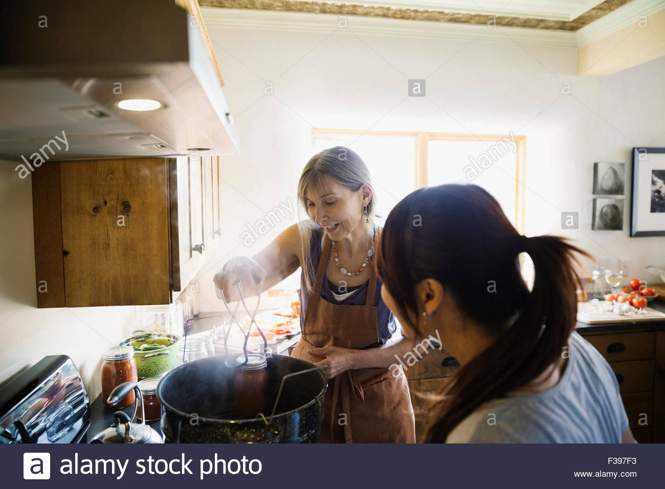 Women canning at stove in kitchen - Stock Image