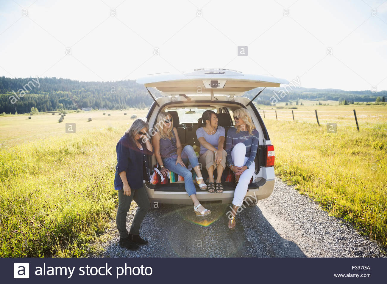 Women sitting in hatchback car sunny rural road - Stock Image