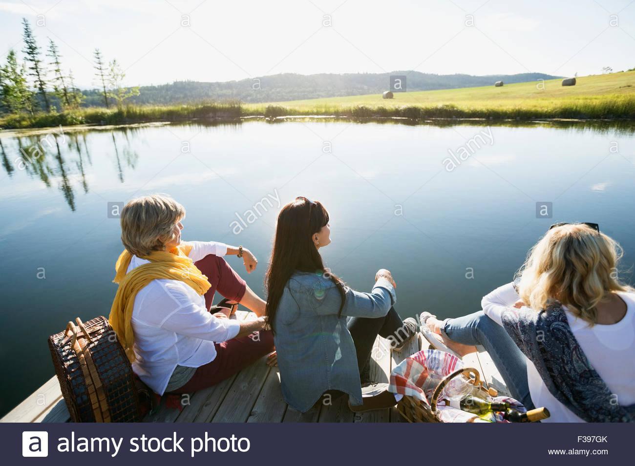 Women enjoying picnic on dock at sunny lakeside - Stock Image