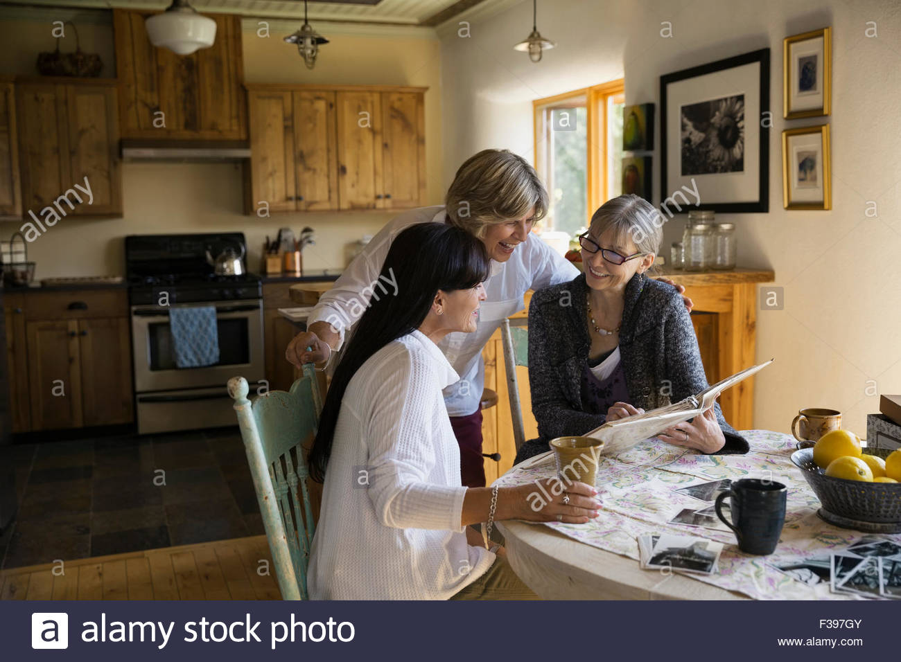 Women looking at photograph album at dining table - Stock Image