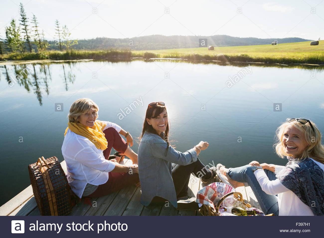 Portrait smiling women enjoying picnic dock sunny lakeside - Stock Image