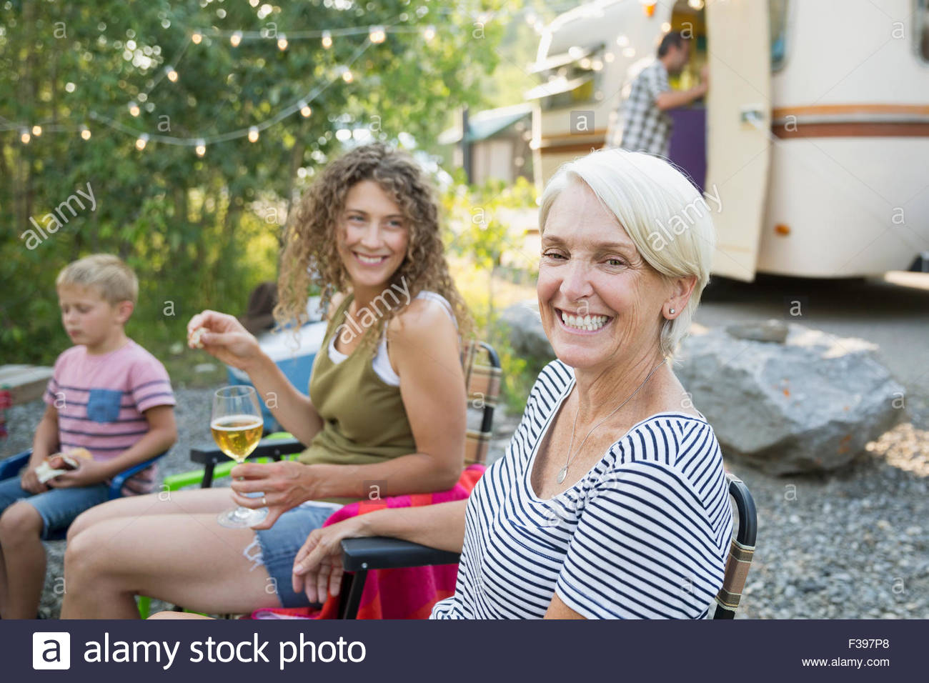 Portrait enthusiastic senior woman camping with family Stock Photo