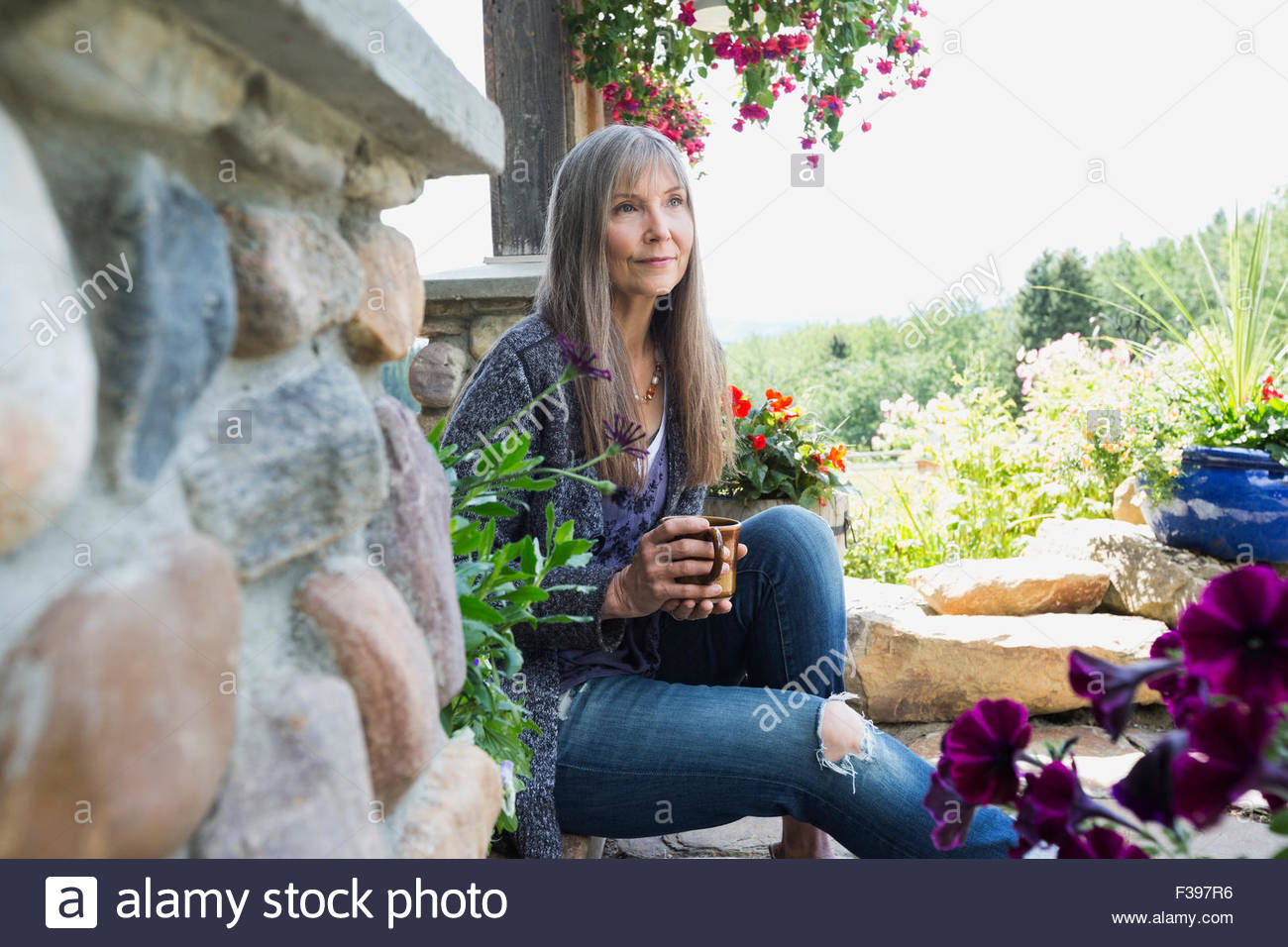 Pensive woman drinking coffee on front stoop - Stock Image