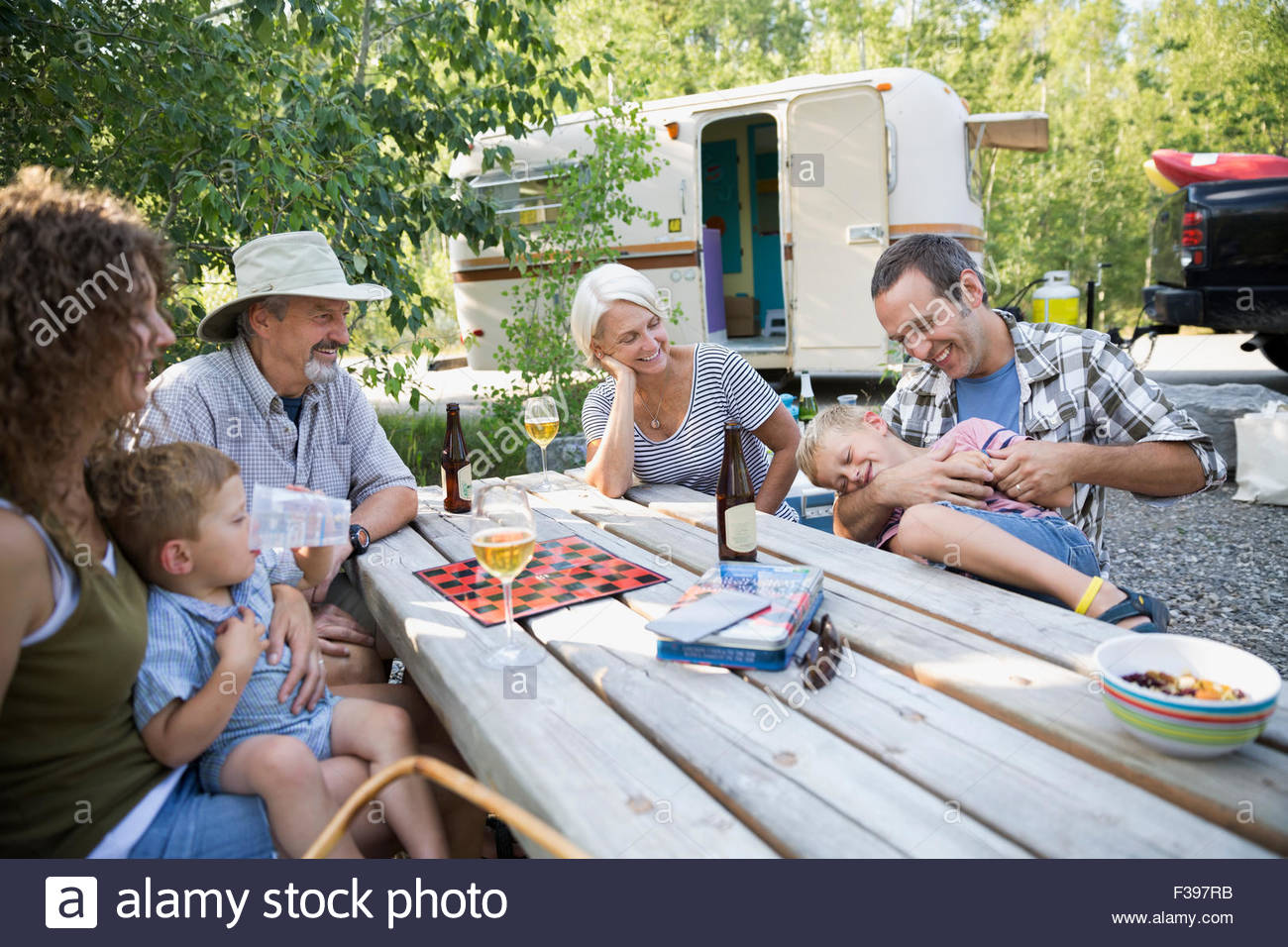 Multi-generation family bonding at campsite picnic table - Stock Image