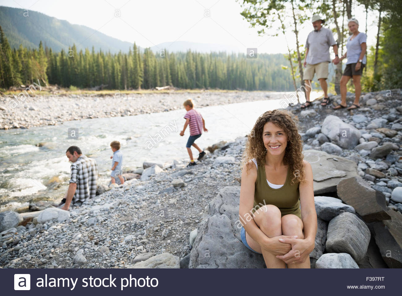 Portrait smiling woman with family at craggy riverside Stock Photo