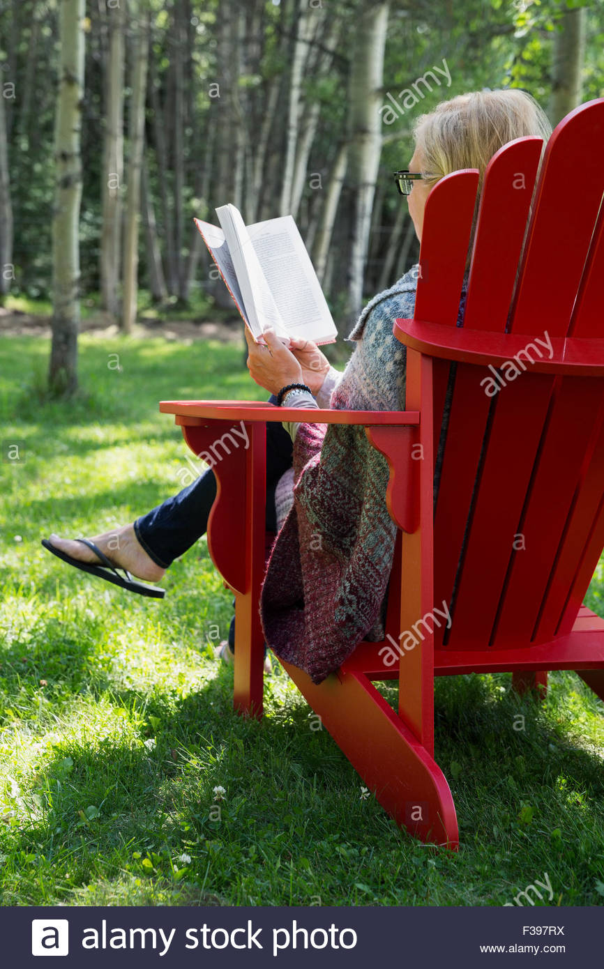 Woman reading book in red adirondack chair - Stock Image