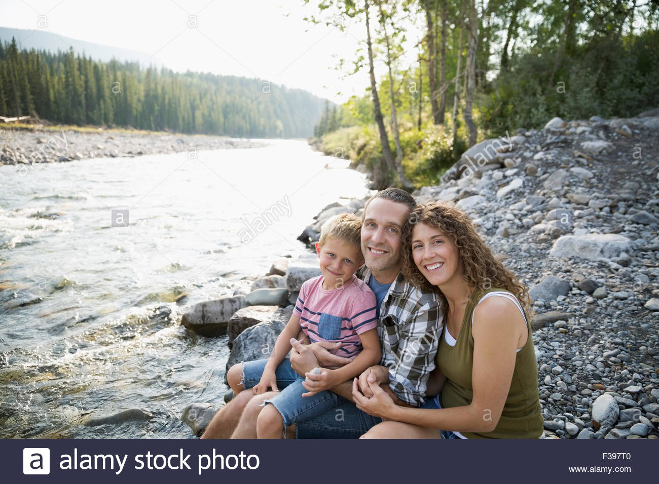 Portrait smiling family at craggy riverside - Stock Image