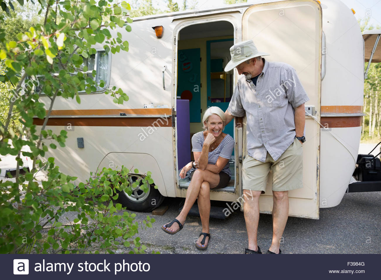 Senior couple at doorway of camper trailer - Stock Image