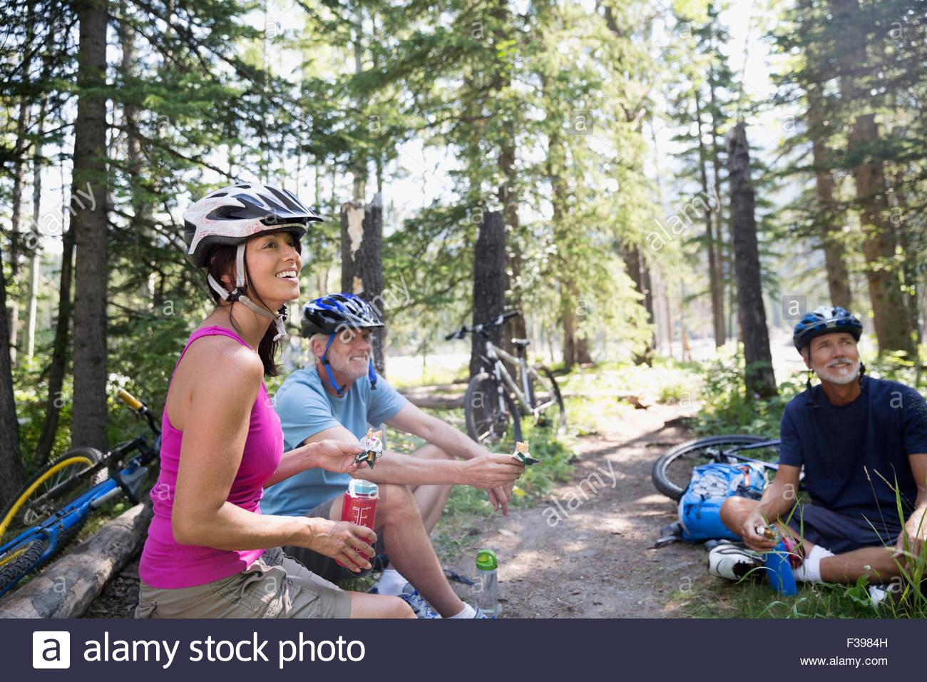 Mountain biking friends taking a break in woods - Stock Image