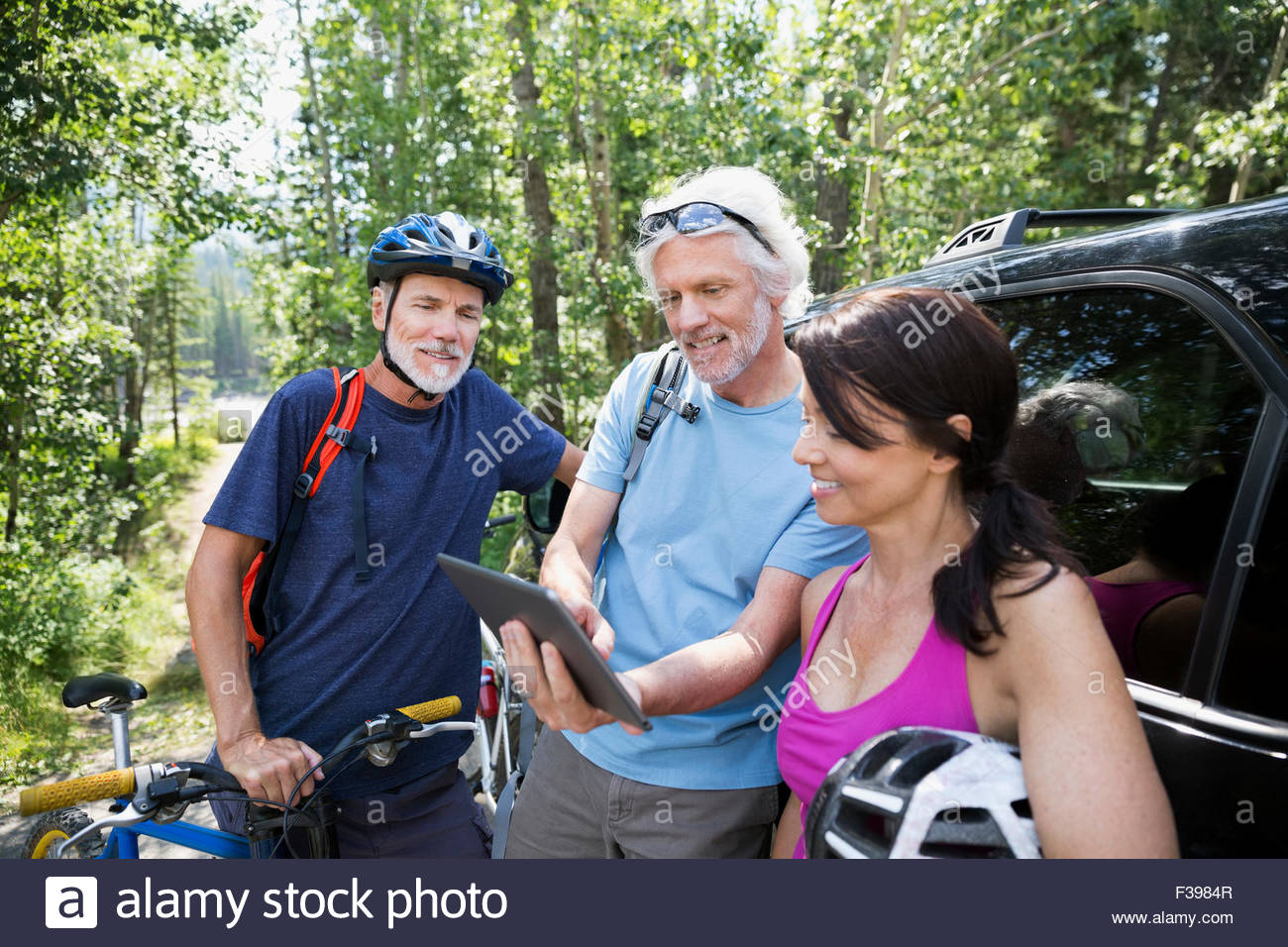 Friends with mountain bike checking digital tablet car - Stock Image