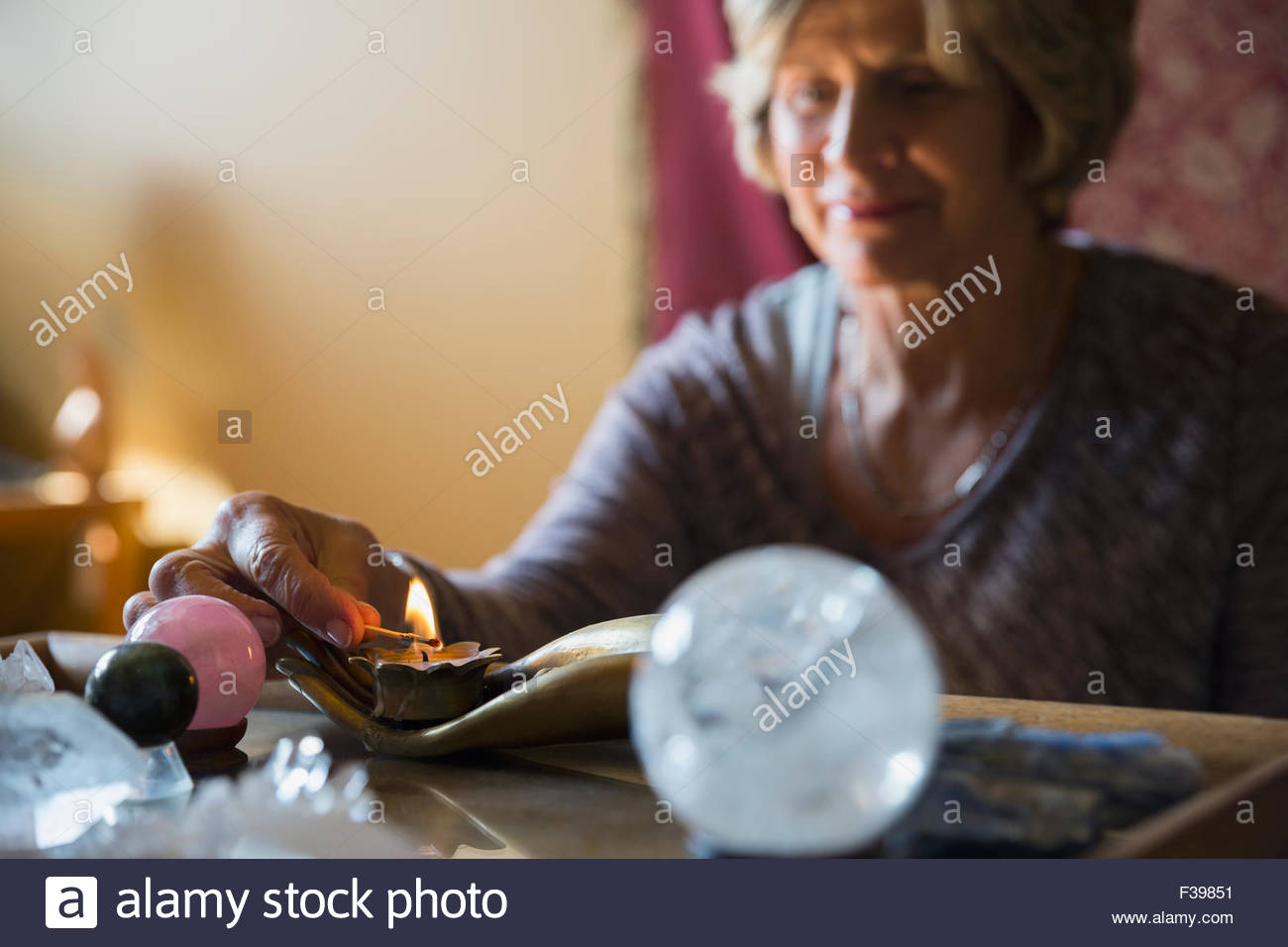 Senior woman lighting candle for meditation - Stock Image