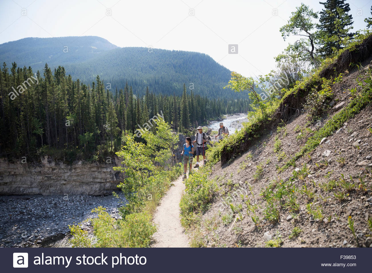 Hikers walking along craggy ridge trail above river - Stock Image
