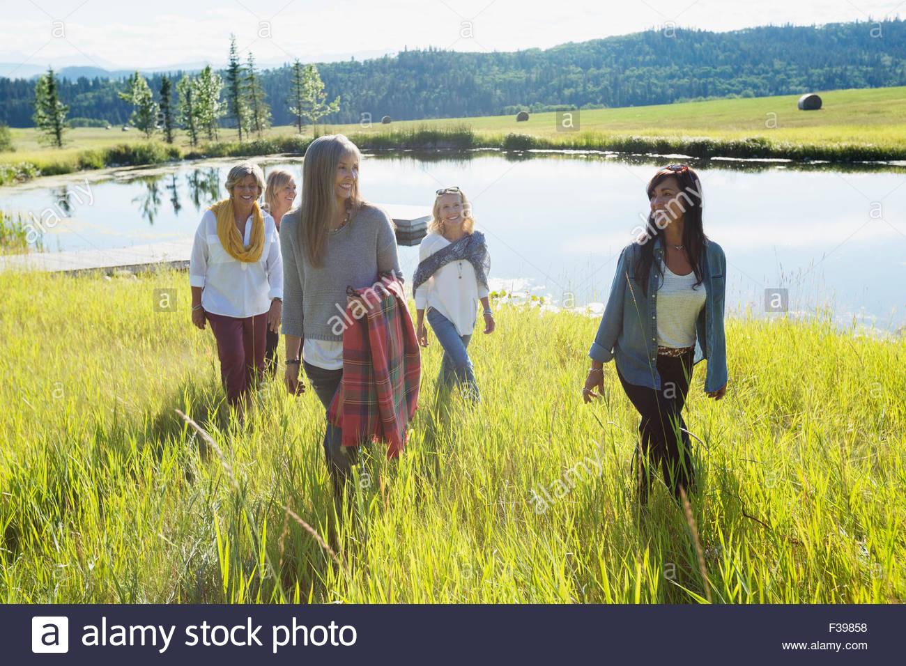 Women walking in sunny grass along lake - Stock Image
