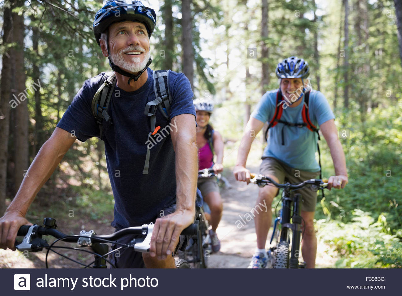 Smiling senior man mountain biking in woods - Stock Image