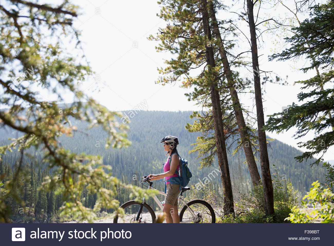 Woman with mountain bike looking view in woods - Stock Image