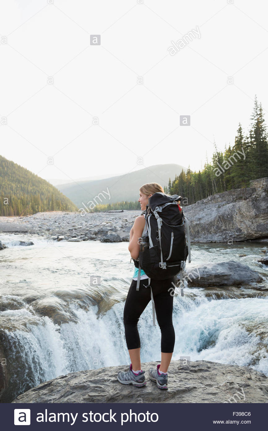 Female hiker with backpack standing at craggy waterfall - Stock Image