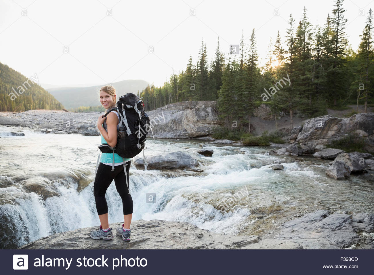 Portrait smiling hiker with backpack at craggy waterfall - Stock Image