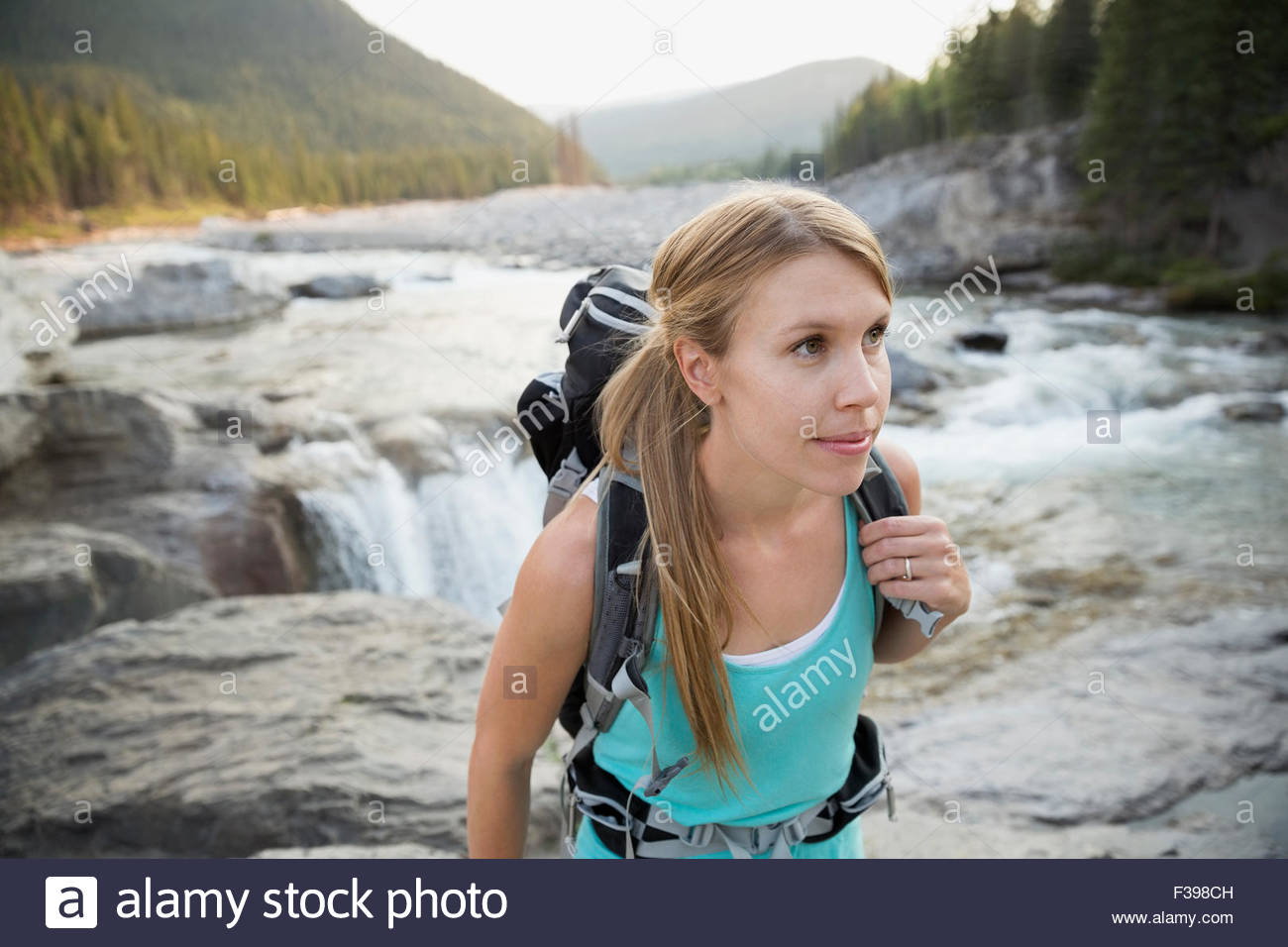 Female hiker with backpack hiking on craggy riverside - Stock Image