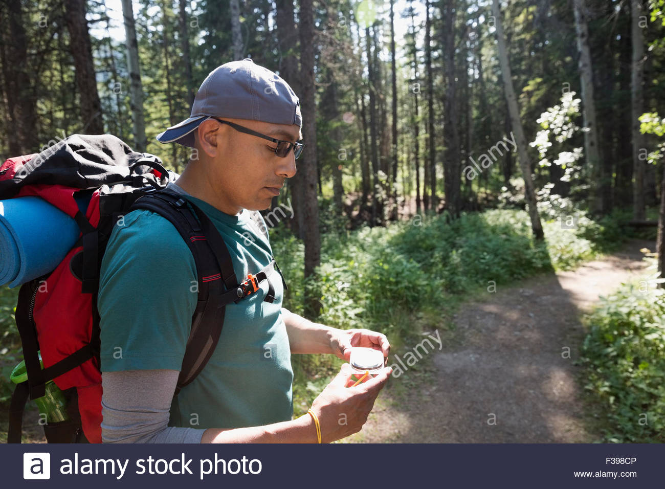 Backpacker checking compass on trail in woods - Stock Image