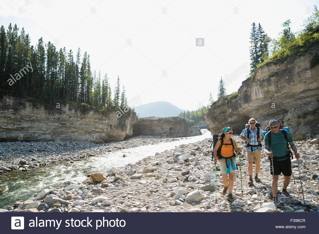 Hikers with backpacks hiking along craggy riverside - Stock Image