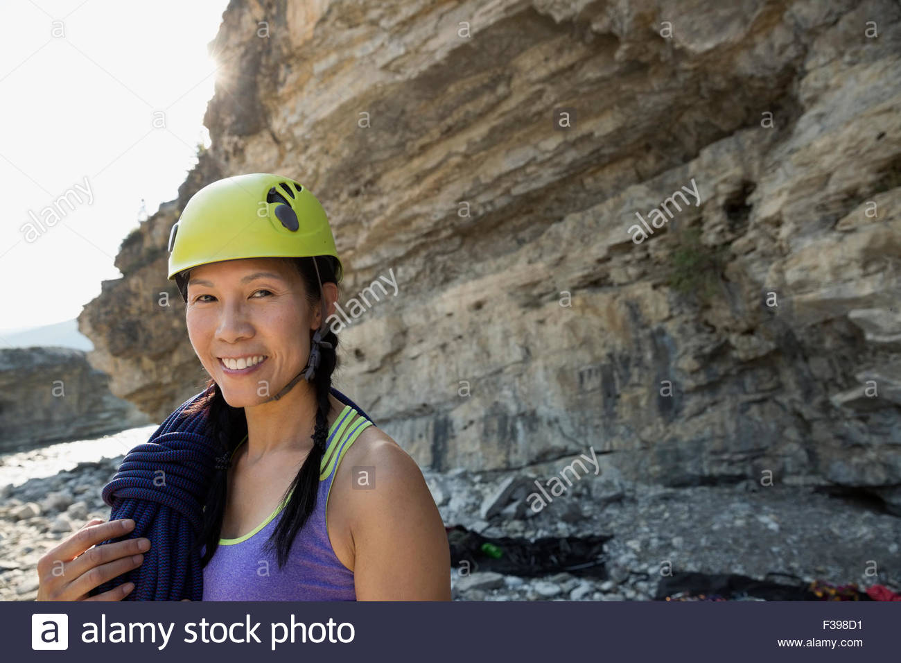 Portrait smiling female rock climber in helmet - Stock Image