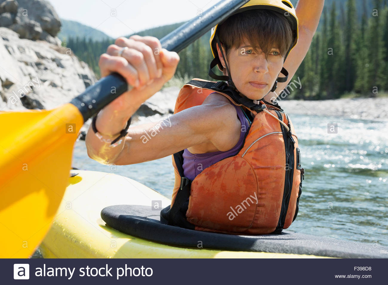 Close up determined woman kayaking in river - Stock Image