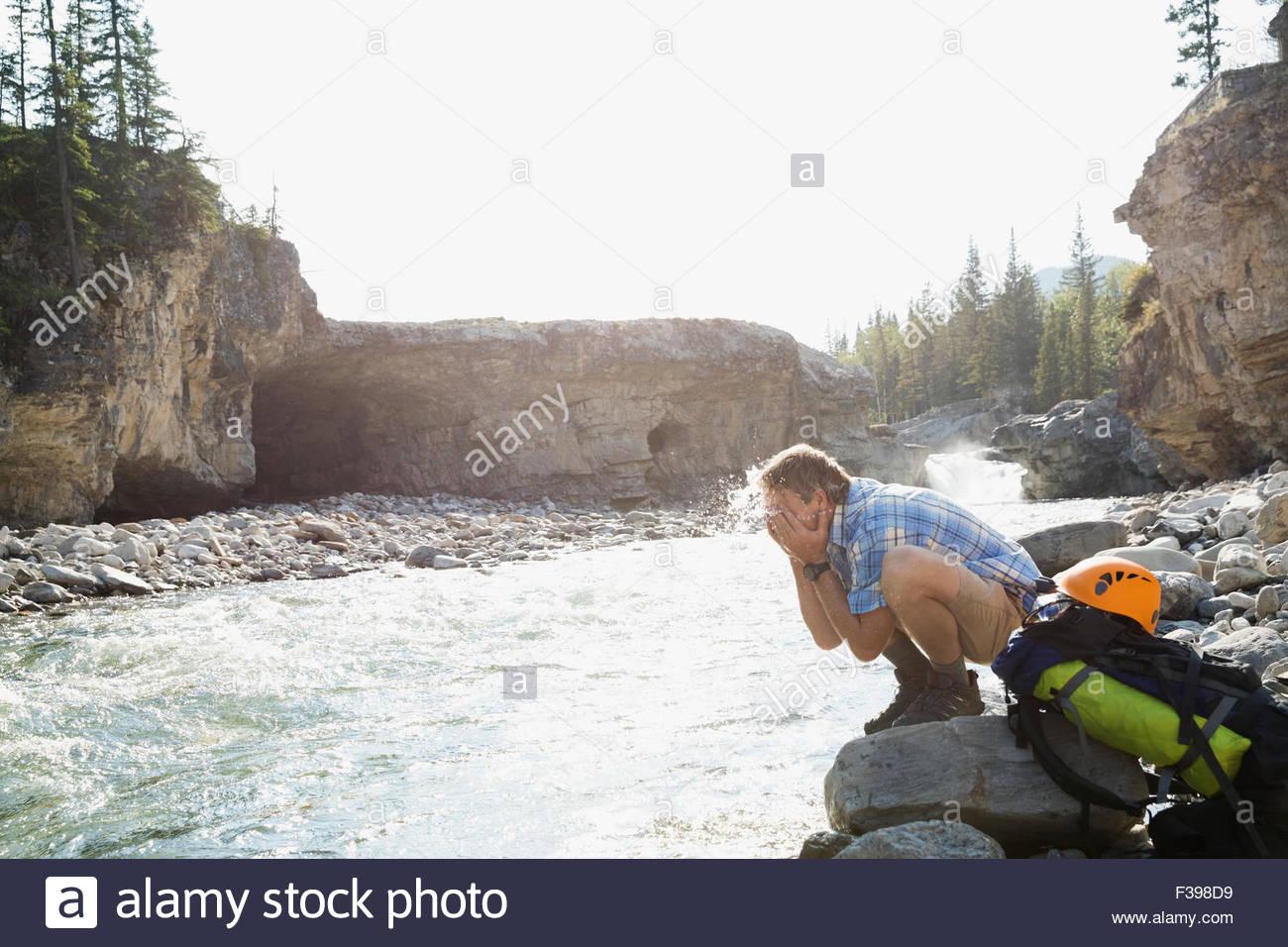 Hiker splashing water on face at craggy riverside - Stock Image