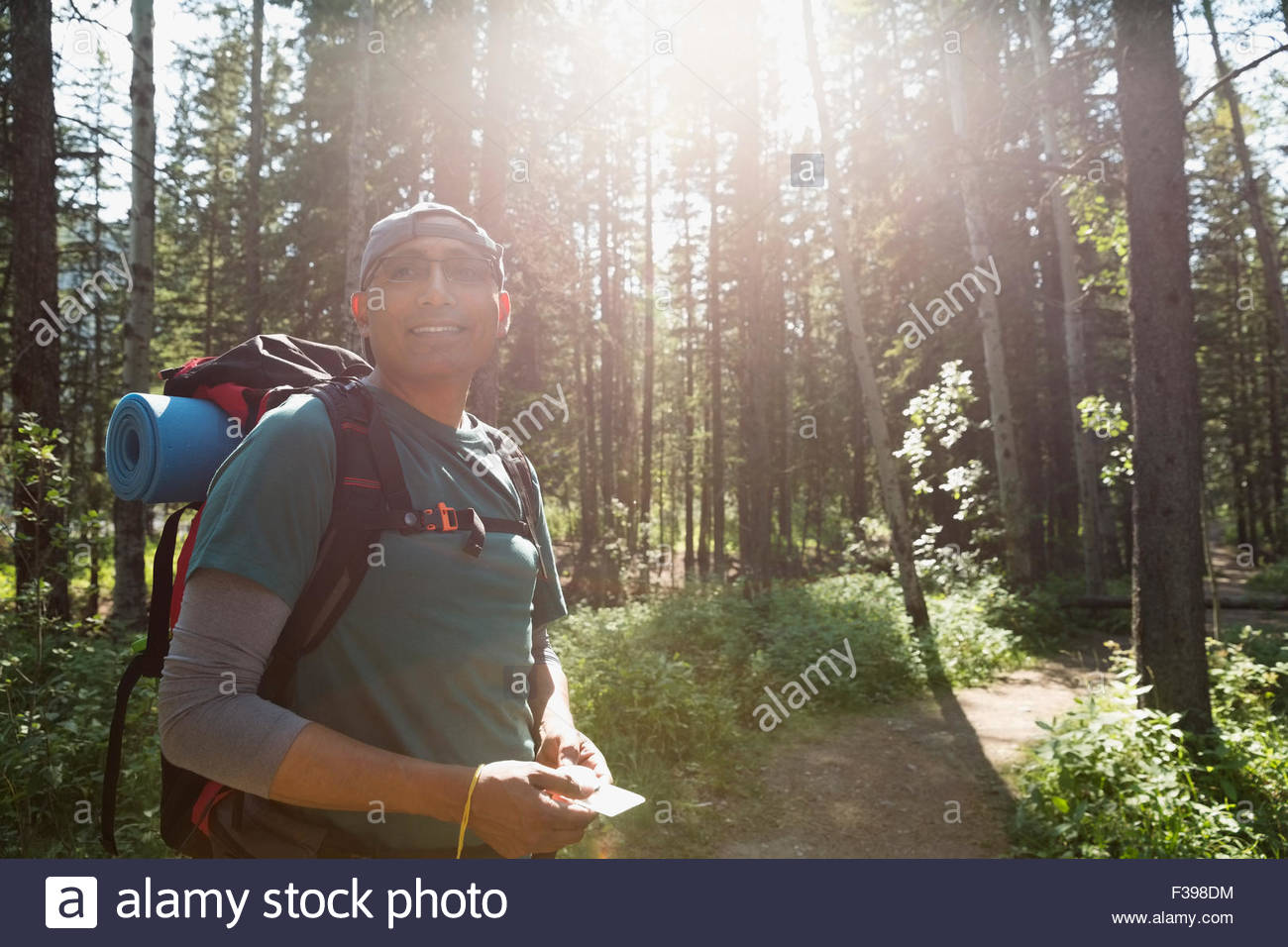Smiling backpacker with compass in sunny woods - Stock Image