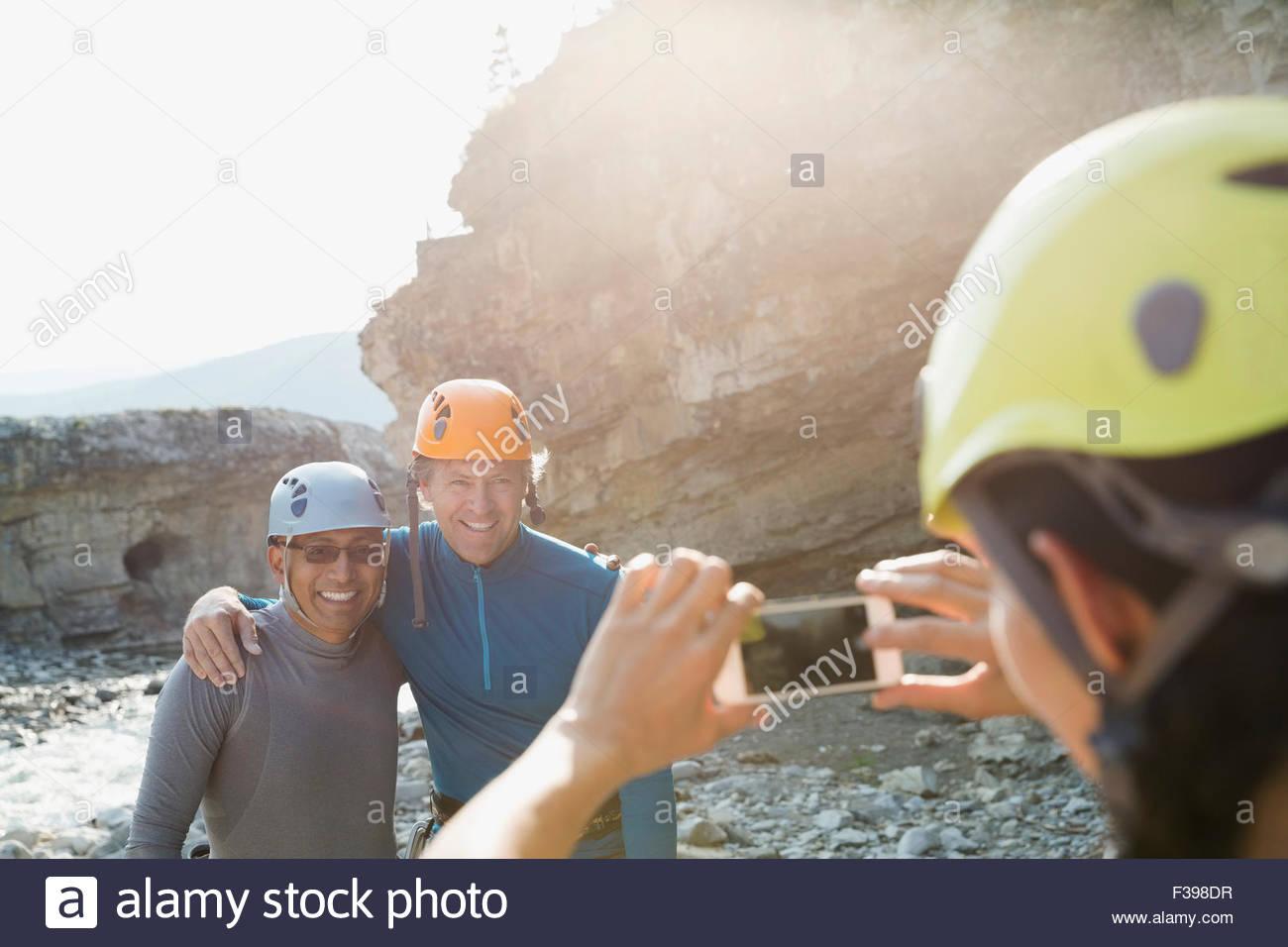 Woman photographing men rock climber helmets - Stock Image