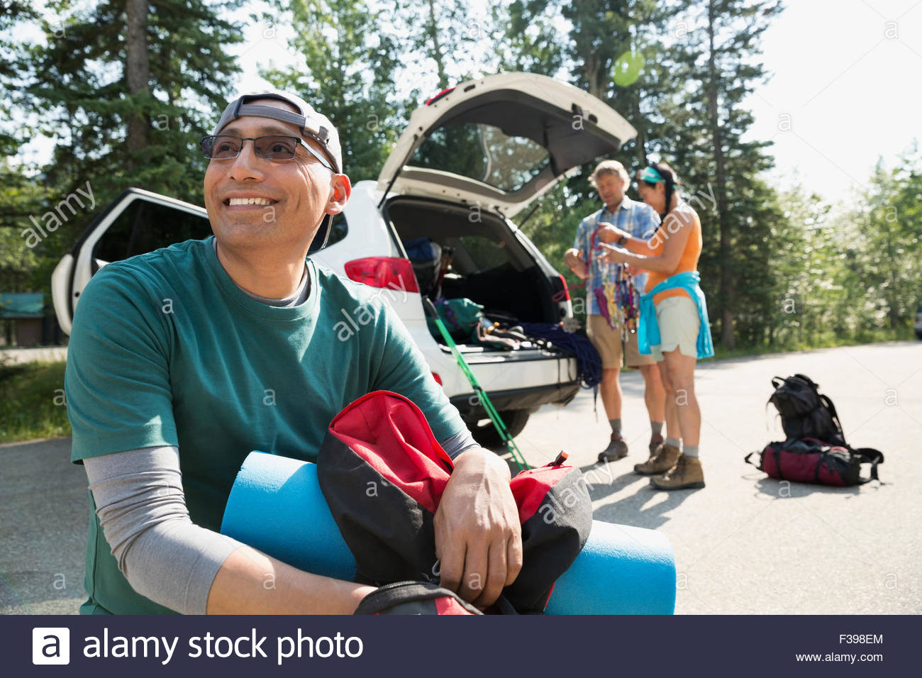 Smiling backpacker near car - Stock Image